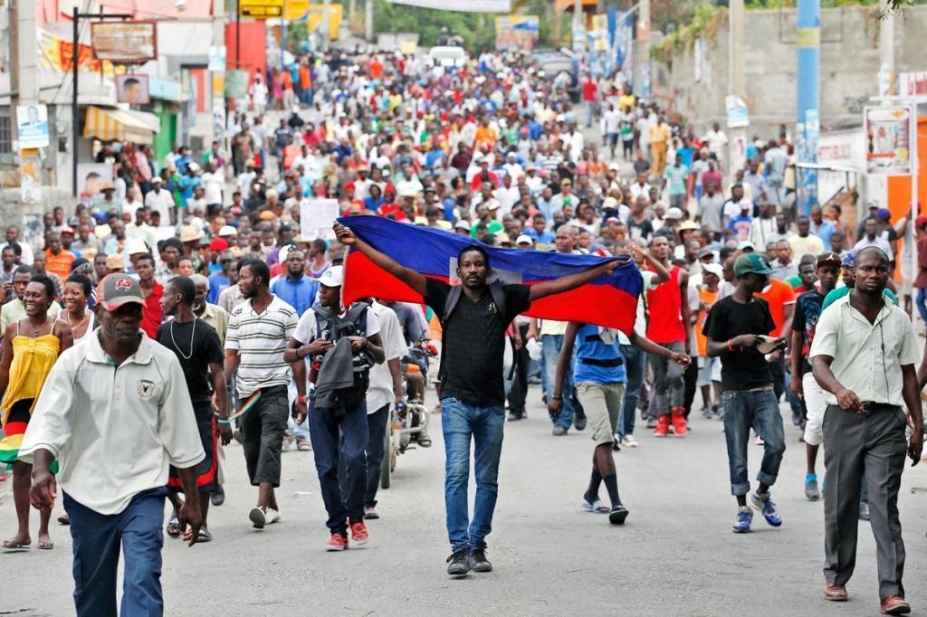 Asistente a una marcha pacífica en Haití sostiene a sus espaldas la bandera de su país